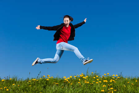 Girl jumping, running against blue sky photo