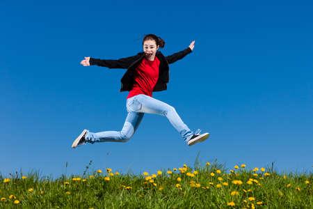 woman jumping: Girl jumping, running against blue sky