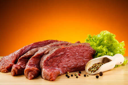 cutting vegetables: Raw beef on cutting board and vegetables