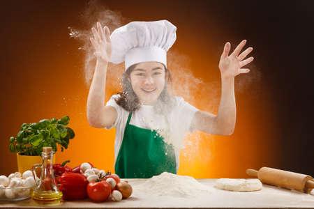ni�os cocinando: Chica haciendo la masa de pizza