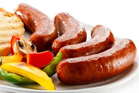 worsten: Gegrilde worstjes, brood en groenten Stockfoto