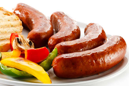 cooked sausage: Grilled sausages, bread and vegetables