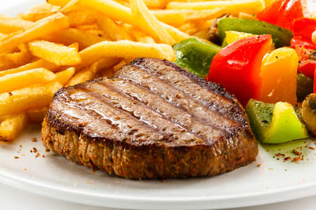 Grilled steak, French fries and vegetables Stock Photo