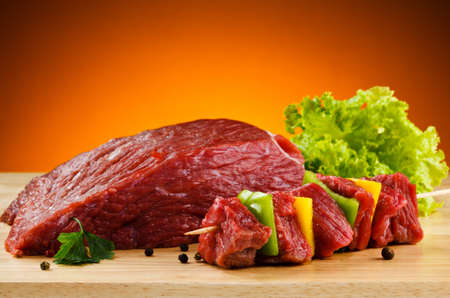 at meat: Raw beef on cutting board and vegetables