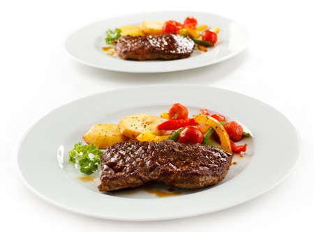 Grilled beefsteaks, baked potatoes and vegetable salad Reklamní fotografie
