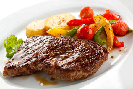 Grilled beefsteaks, baked potatoes and vegetable salad photo
