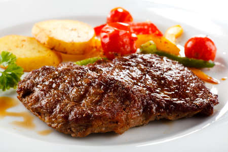 sirloin steak: Grilled beefsteaks, baked potatoes and vegetable salad