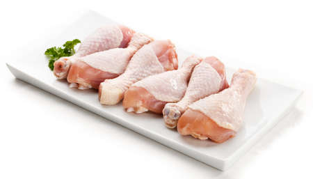 Raw chicken legs on white background photo