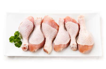 Cosce di pollo crudo su sfondo bianco