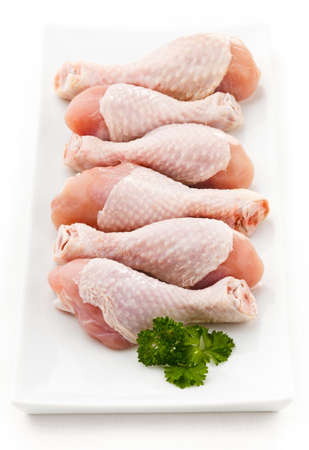 carniceria: Piernas de pollo crudo en el fondo blanco Foto de archivo