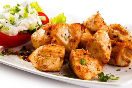 pollos asados: Carne a la brasa y verduras en el fondo blanco