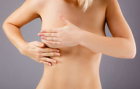 woman naked body: Woman examining her breast Stock Photo