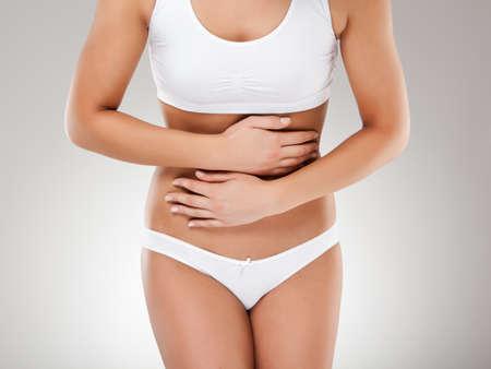 dolor de estomago: Mujer masajear dolor de estómago Foto de archivo