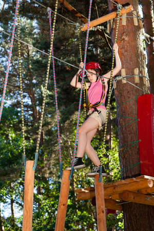 Girl climbing in adventure park photo