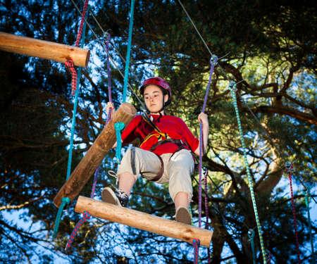 登る: 少女の冒険公園でのクライミング 写真素材