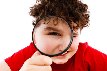 Boy looking through magnifying glass isolated on white photo