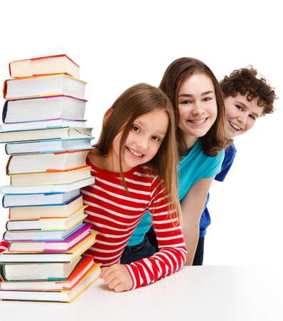 Students peeking behind pile of books on white photo
