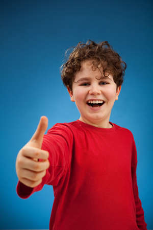 Portrait of young boy showing ok sign photo
