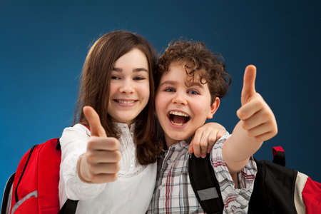 schoolgirls: Students showing OK sign on blue background Stock Photo