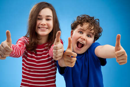 Kids showing OK sign on blue background photo