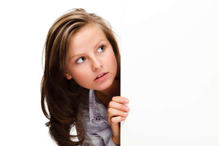 Young attractive girl behind empty board on white background photo
