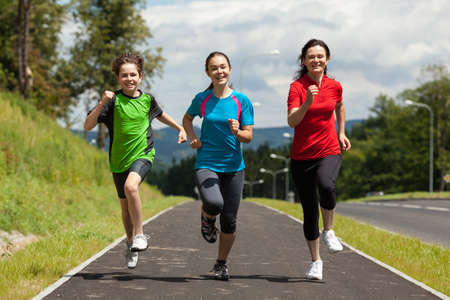 run woman: Active family - mother and kids running outdoor