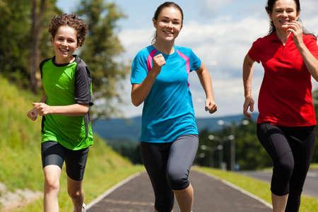 Activo familia - madre y los niños corriendo al aire libre