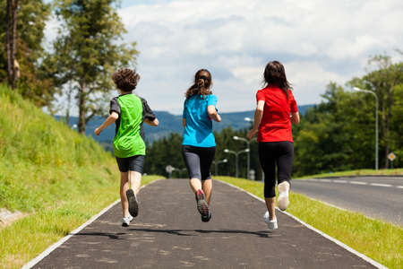 leap: Active family - mother and kids running outdoor