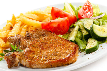 Grilled steak, French fries and vegetables photo