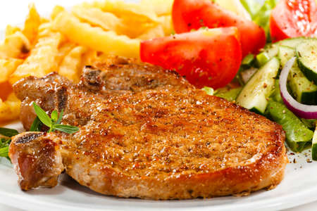 pork chop: Grilled steak, French fries and vegetables Stock Photo