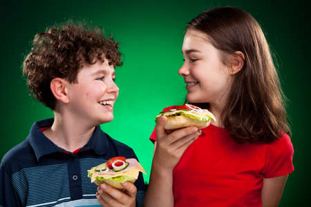 Kids eating big sandwiches photo