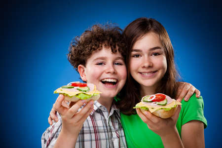 Kids eating big sandwiches