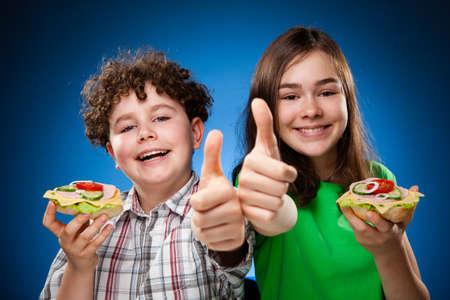 ni�os comiendo: Ni�os que comen s�ndwich grande que muestra signo de OK