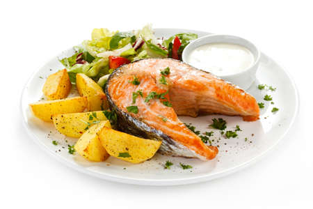 Grilled salmon, baked potatoes and vegetables photo