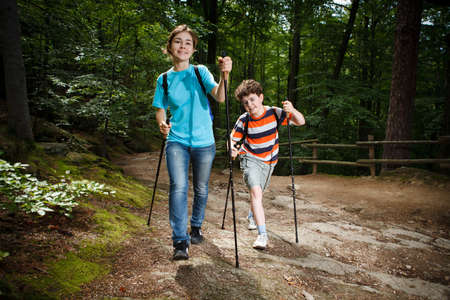 hike: Girl and boy walking in forest Stock Photo