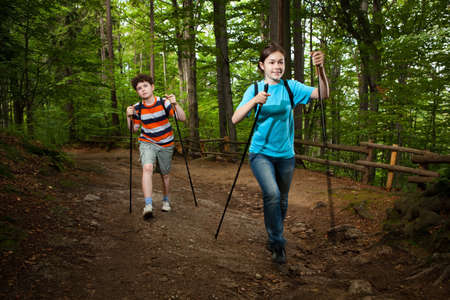 Girl and boy walking in forest photo