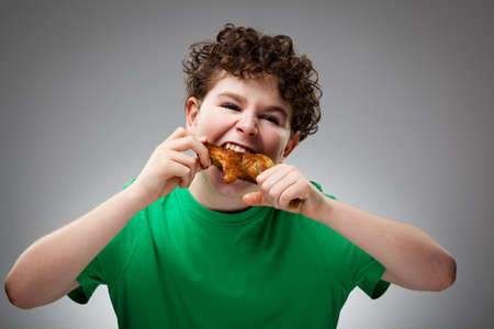 Boy eating roasted chicken leg photo