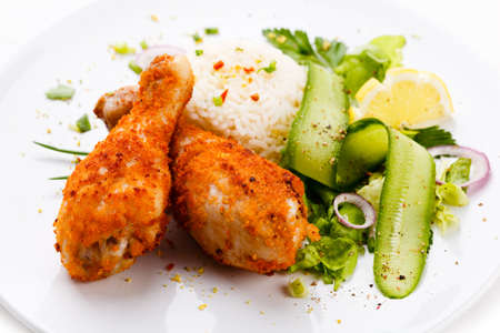 Roasted chicken drumsticks, rice and vegetables photo