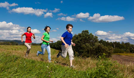 Actieve familie - moeder en kinderen rennen, springen outdoor Stockfoto