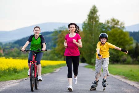 riding bike: Famiglia attiva - madre e bambini che corrono, ciclismo, pattinaggio
