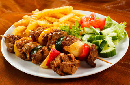 shish: Grilled meat, French fries and vegetables Stock Photo