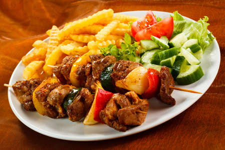 prepared food: Grilled meat, French fries and vegetables Stock Photo