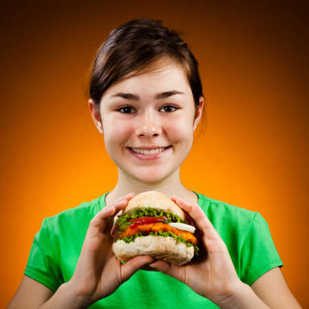 Girl eating big hamburger photo