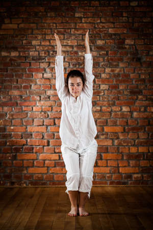 Woman exercising yoga against brick wall Stock Photo - 17993504