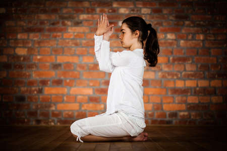 Woman exercising yoga against brick wall Stock Photo - 17993501