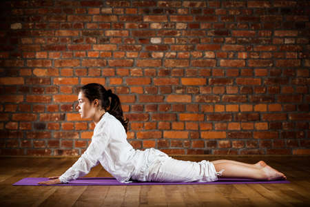 Woman exercising yoga against brick wall Stock Photo - 17993509