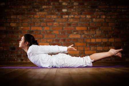 Woman exercising yoga against brick wall Stock Photo - 17993505