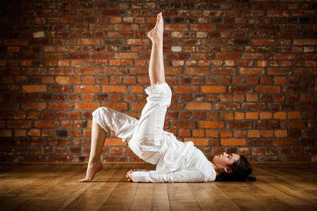 practicing: Woman exercising yoga against brick wall
