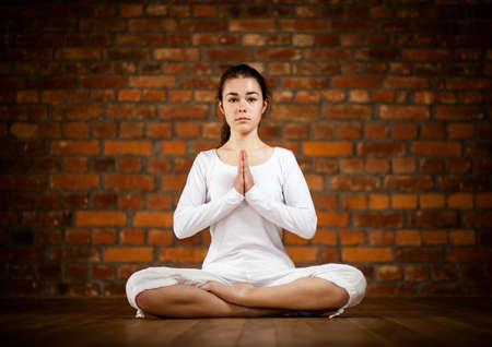 Woman exercising yoga against brick wall Stock Photo - 17993497