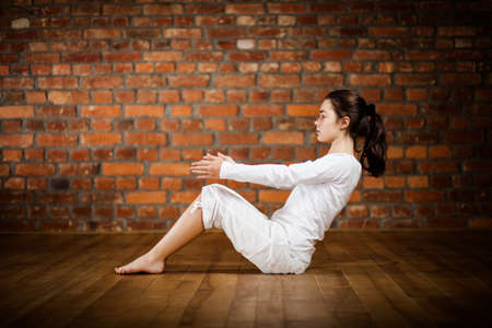 Woman exercising yoga against brick wall photo